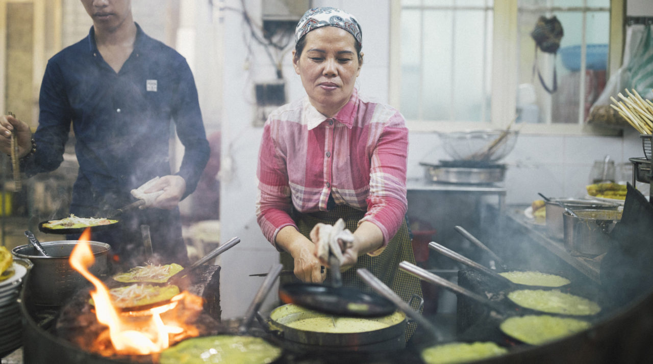 A local cook is making Bánh Xèo (also known as Vietnamese pancake)