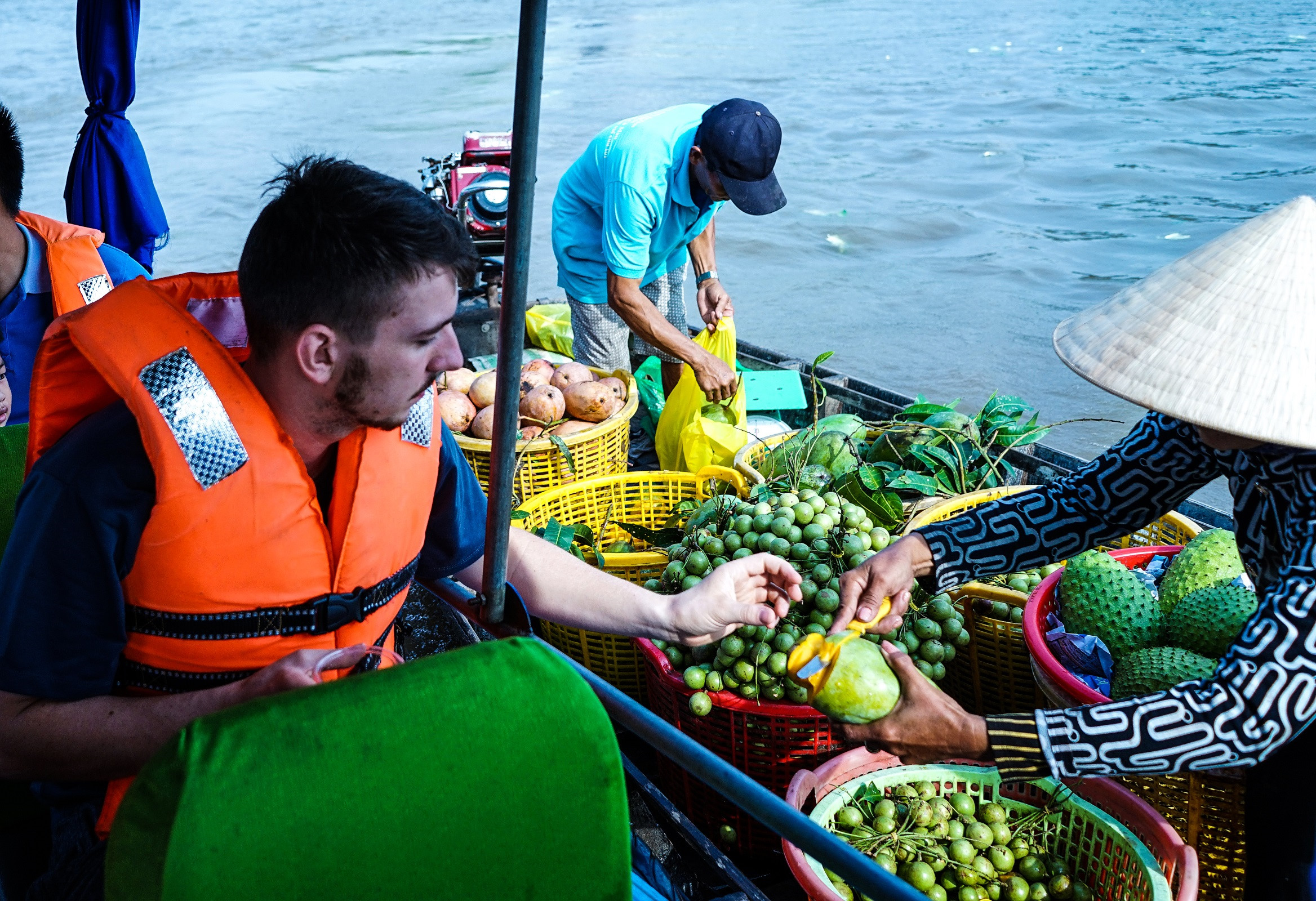 a-traveler-taste-and-buy-fruit-at-cai-rang-floating-market-in-just-a-minute-saigon-riders