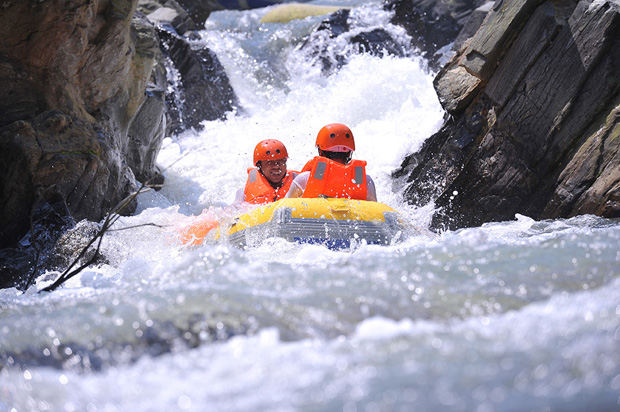 Two people at a time on a plastic boat to sliding through canyons of the waterfalls